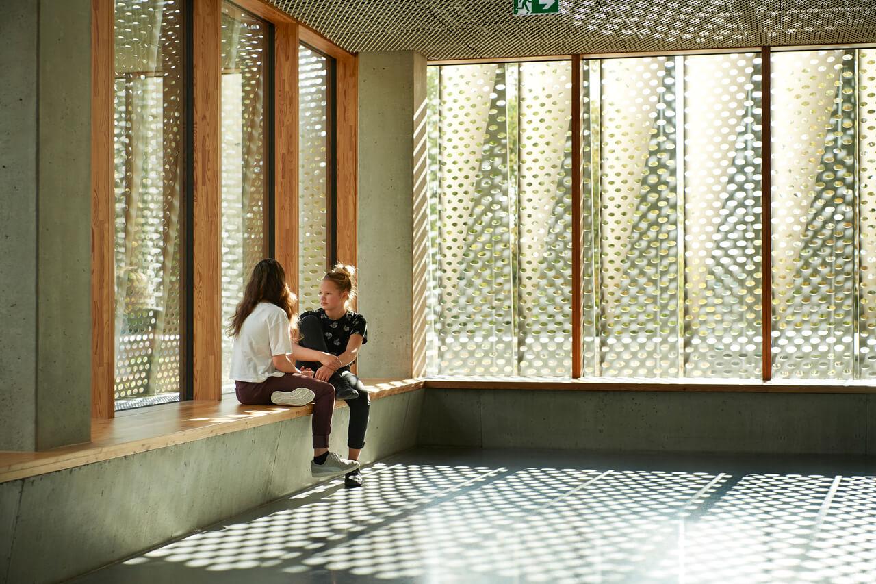 Zwei Mädchen, die in der Schulhalle sitzen, was durch natürliches Licht belichtet ist