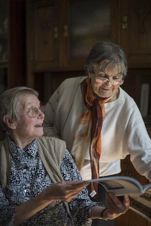 Zwei ältere Damen, die über eine Zeitschrift sich besprechen