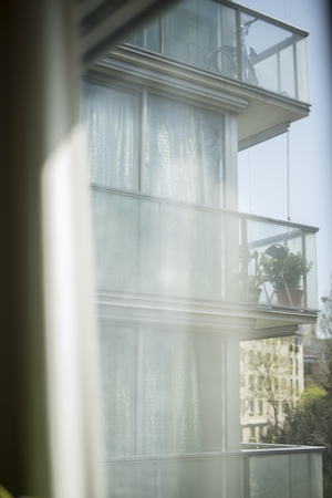 Winkelsicht einer Gebäudefassade mit Fenstern, die im Sonnenlicht lassen